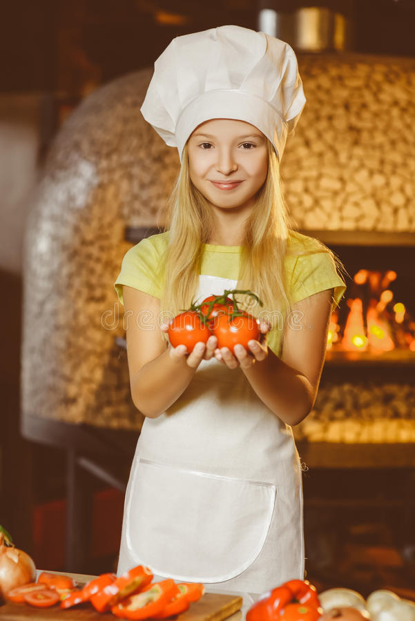 Смешная усмехаясь девушка шеф-повара держа томаты на стоковые фото