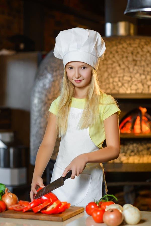 Смешная усмехаясь девушка шеф-повара режет перец на ресторане стоковые фотографии rf