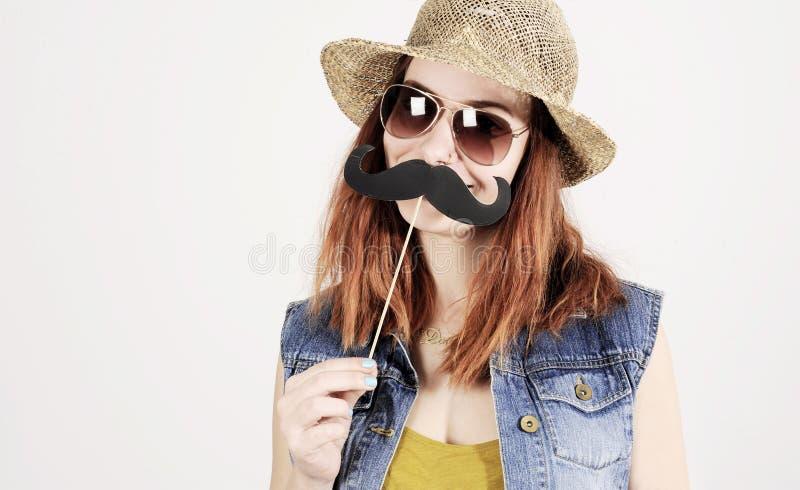 Смешная ультрамодная девушка битника при бумажный усик играя с эмоцией стоковое изображение