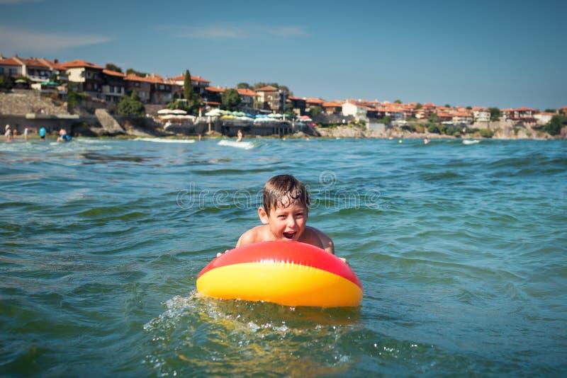 Смешное жизнерадостное заплывание мальчика в воде на раздувном тюфяке стоковое изображение rf
