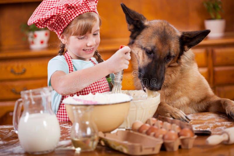 Смешное изображение маленькой девочки которая запачкает тесто, и немец стоковые фотографии rf