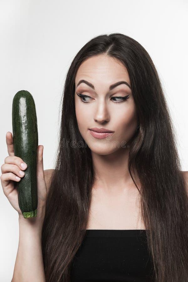 Смешное изображение молодой женщины держа цукини стоковое изображение