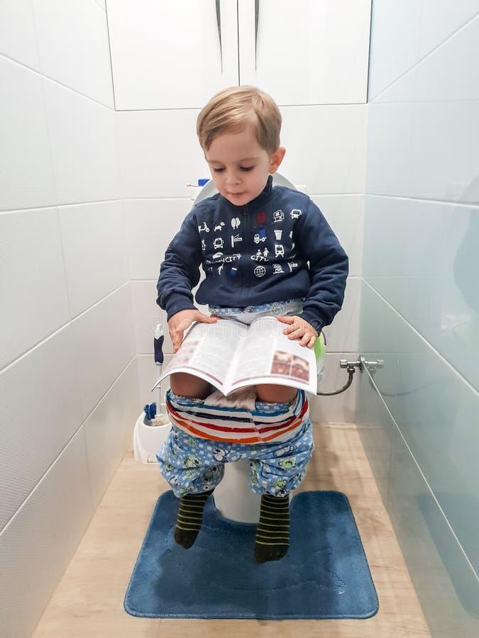 Смешное изображение немного 3 старого лет мальчика малыша сидя на туалете и читая журнал стоковые фото