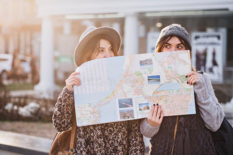 Смешное положительное изображение модных девушек на солнечной улице имея потеху в городе, пряча за citymap Путешествовать стоковые фото