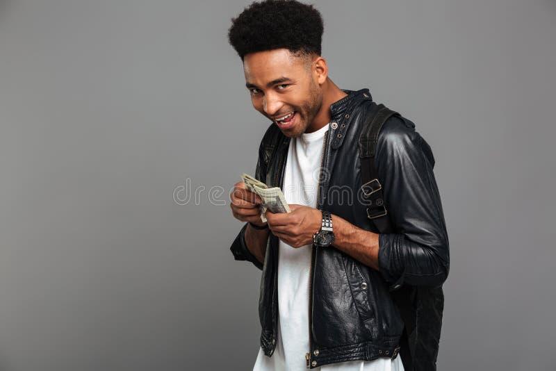 Смешной африканский человек с стильной стрижкой жадно рассматривает деньги, стоковое изображение rf