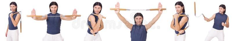 Смешной боец карате с nunchucks на белизне стоковое фото