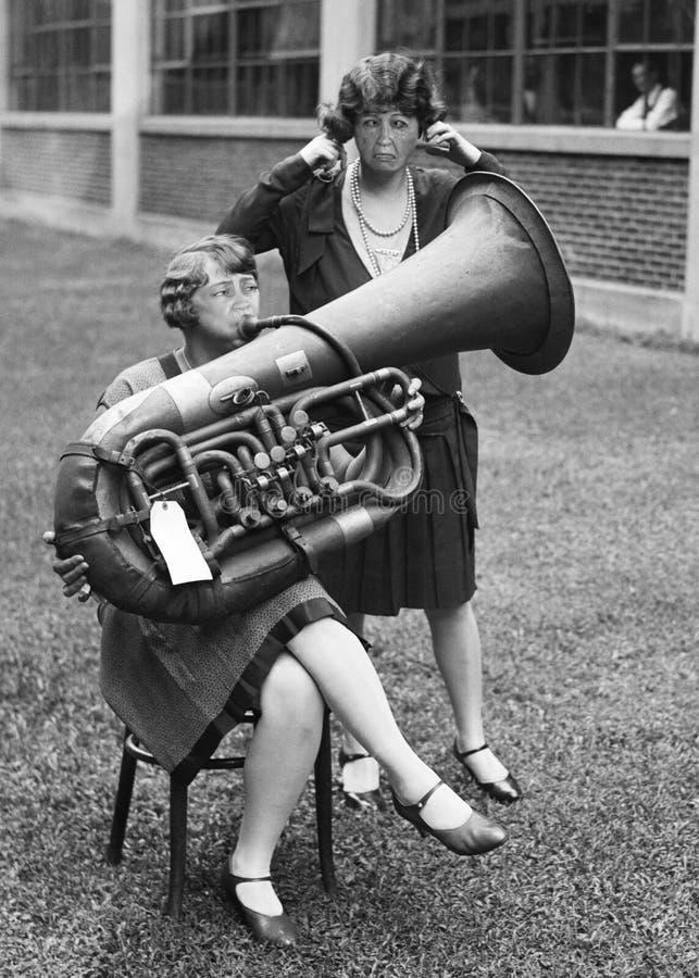 Смешной винтажный игрок тубы, музыка, женщины имея потеху стоковые изображения