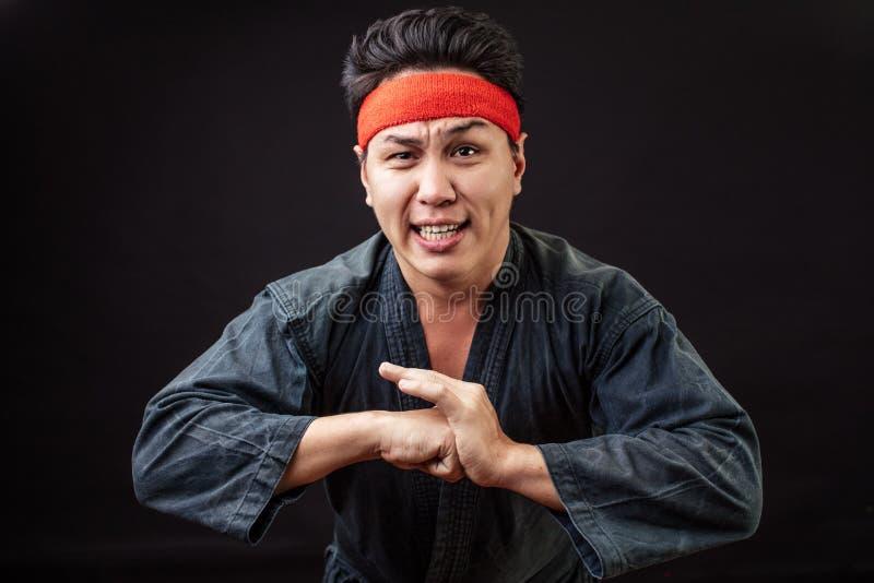 Смешной вспугнутый боец карате нося черное кимоно стоковое изображение