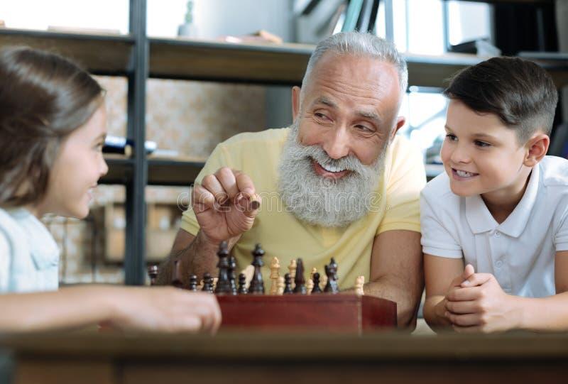 Смешной дед усмехаясь пока играющ шахмат с детьми стоковые фотографии rf