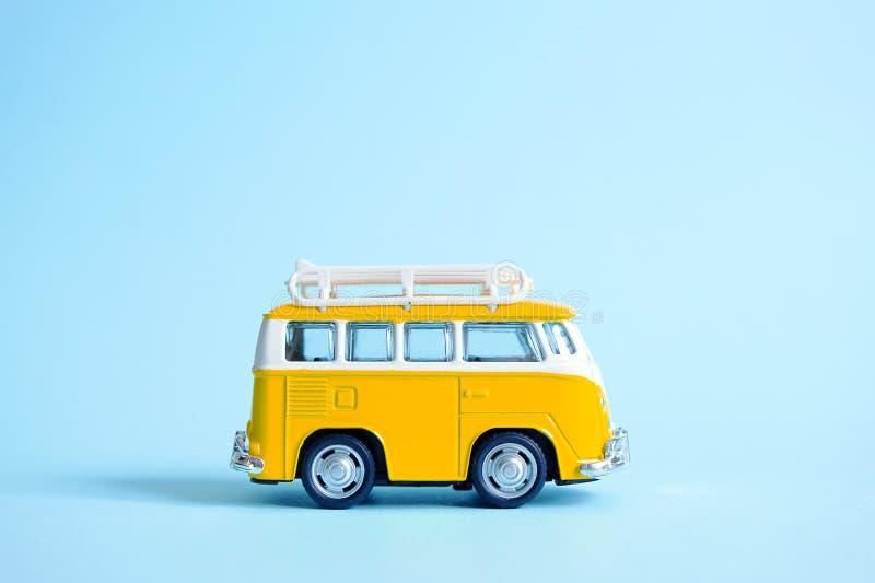 Смешной желтый ретро автомобиль с surfboard на голубой предпосылке Концепция каникул перемещения лета Поездка Автомобиль минифург стоковые изображения rf