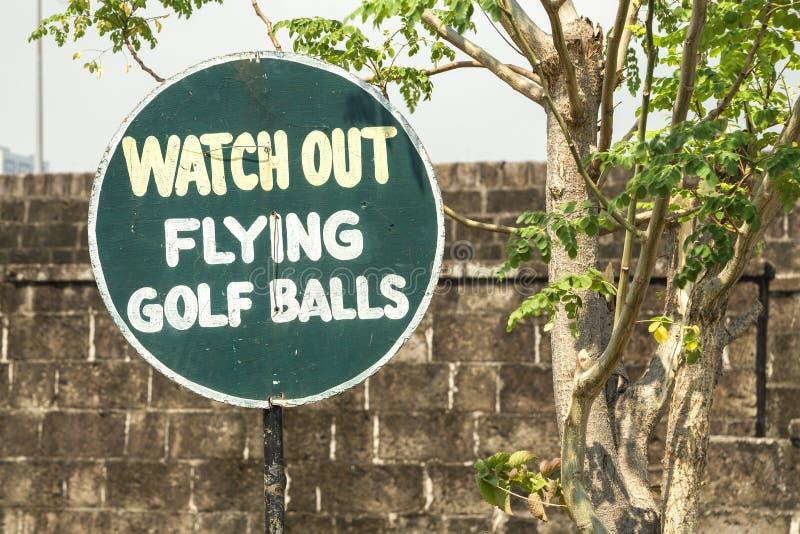 Смешной знак наблюдает вне, летающ шары для игры в гольф в поле для гольфа стоковое изображение rf