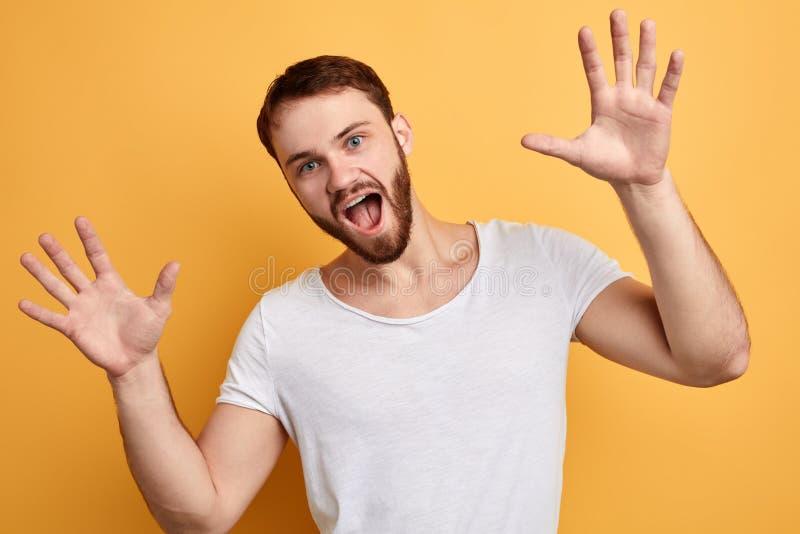 Смешной красивый парень с широким открытым ртом вытягивая ладони к стоковые фотографии rf
