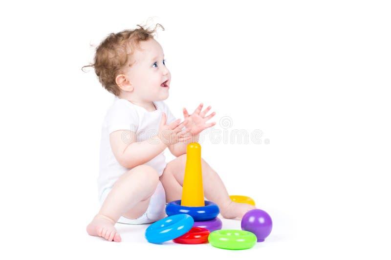 Смешной курчавый младенец играя с пластичной пирамидой стоковые изображения rf