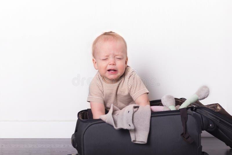 Смешной малыш сидя в чемодане и пробуя упаковать его Милый ребенок идя отдохнуть стоковые изображения rf