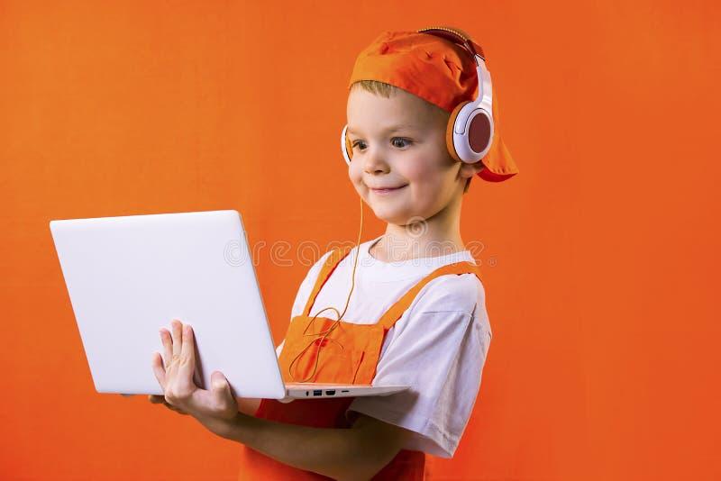 Смешной мальчик в равномерном построителе и наушниках смотря компьтер-книжку стоковая фотография rf