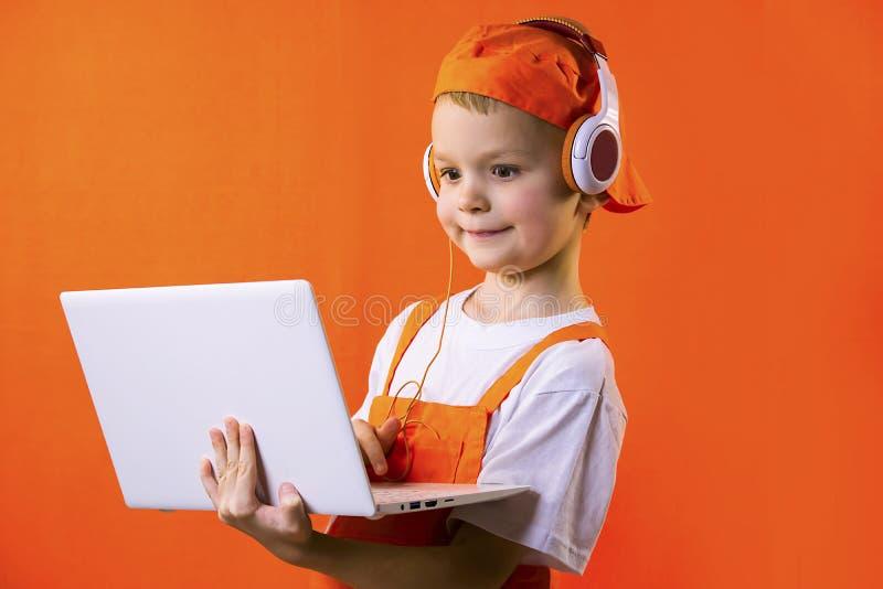 Смешной мальчик в равномерном построителе и наушниках смотря компьтер-книжку стоковая фотография