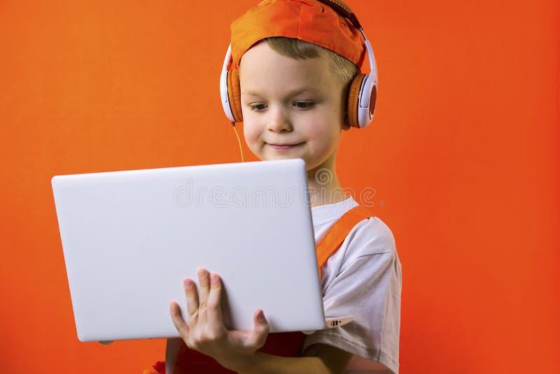 Смешной мальчик в равномерном построителе и наушниках смотря компьтер-книжку стоковые фотографии rf