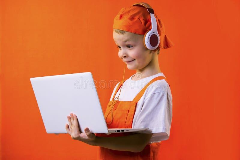 Смешной мальчик в равномерном построителе и наушниках смотря компьтер-книжку стоковые изображения rf