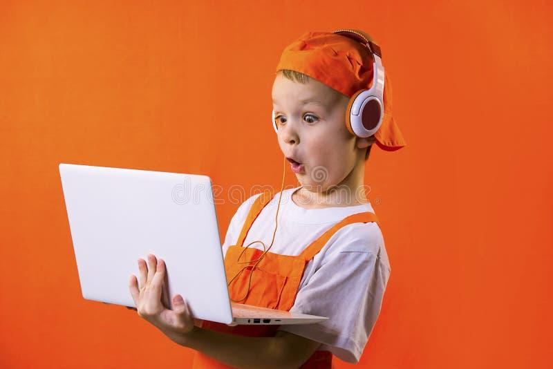Смешной мальчик в равномерном построителе и наушниках смотря компьтер-книжку стоковое фото