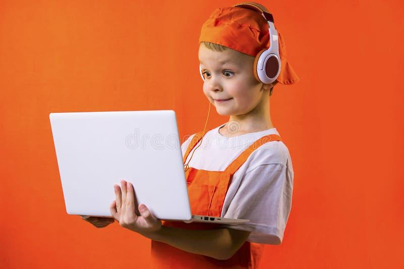 Смешной мальчик в равномерном построителе и наушниках смотря компьтер-книжку стоковое изображение rf