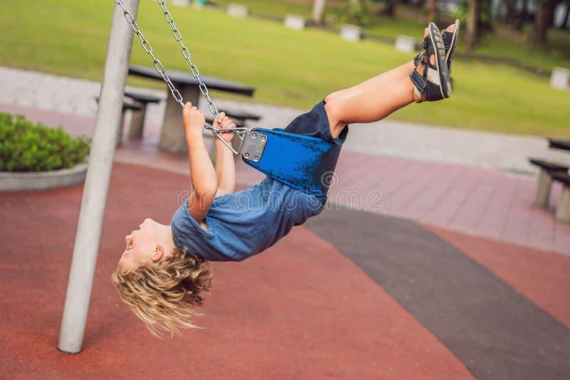 Смешной мальчик ребенк имея потеху с цепным качанием на внешней спортивной площадке ребенок отбрасывая на теплый день Активный от стоковые фото