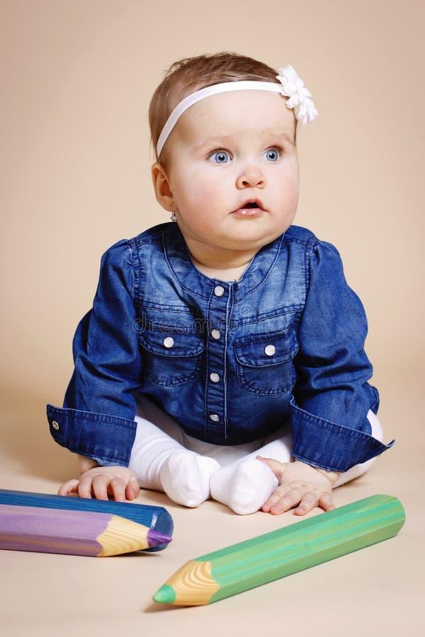 Смешной маленький малыш с большими карандашами стоковая фотография