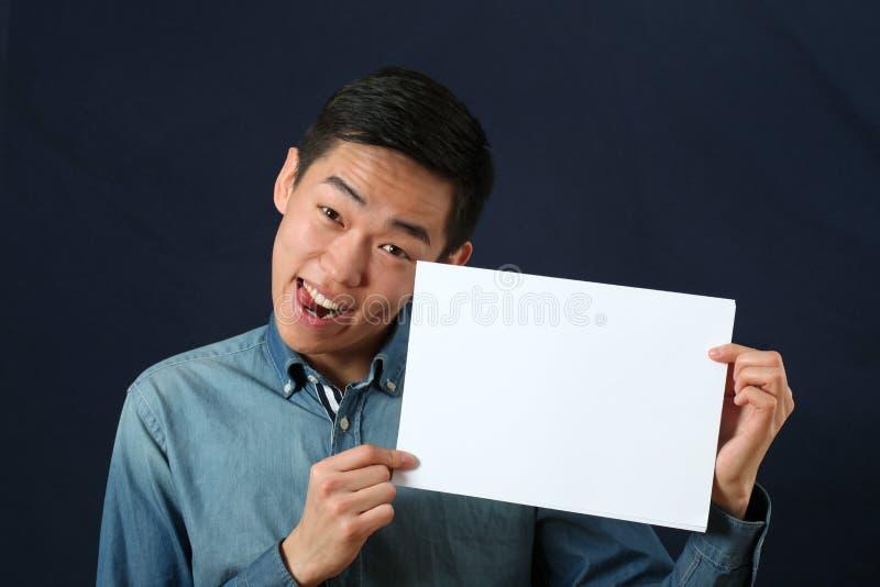 Смешной молодой азиатский человек показывая страницу космоса экземпляра стоковое фото rf