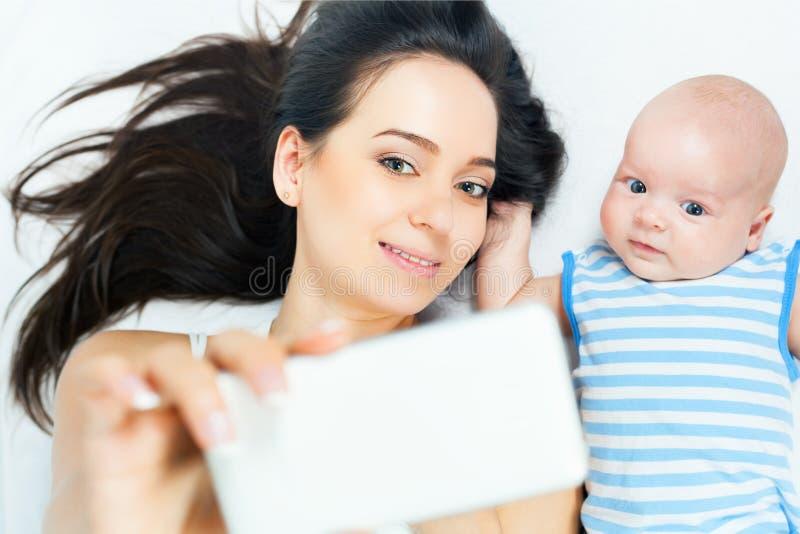 Смешной младенец и мать делают selfie на мобильном телефоне стоковое изображение rf