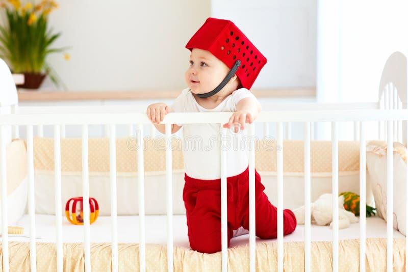 Смешной младенец с корзиной игрушки как шлем в его кроватке стоковое фото rf