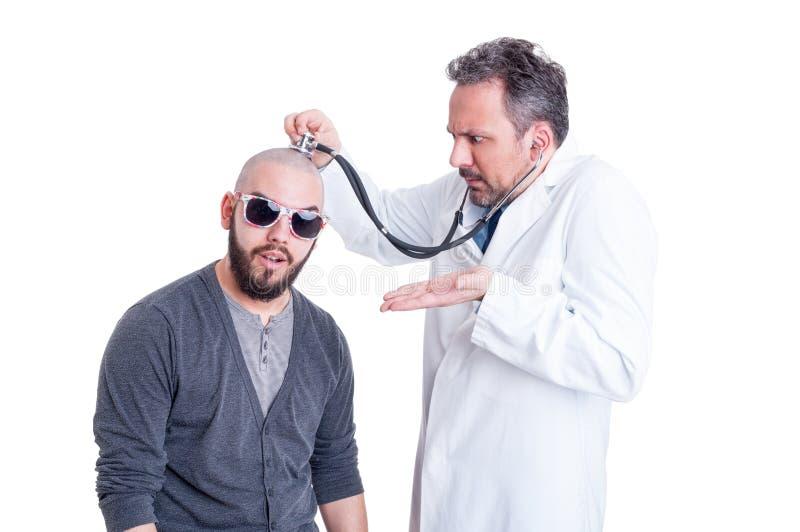 Смешной доктор проверяя придурковатого пациента с головной проблемой стоковое фото