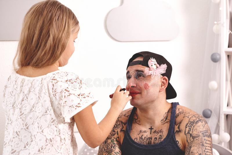 Смешной отец Tattoed времени в крышке и его ребенок играют дома Милая девушка делает макияж к ее папе в ей стоковое фото