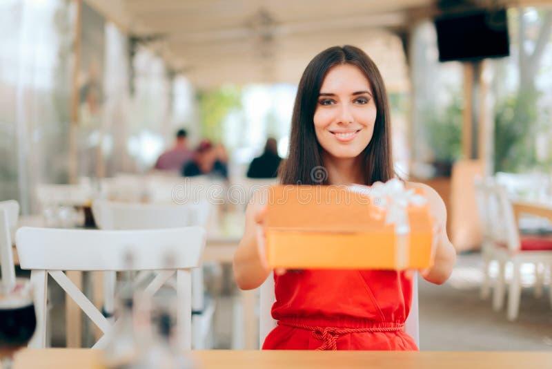 Смешной подарок на день рождения удерживания женщины в ресторане стоковая фотография rf