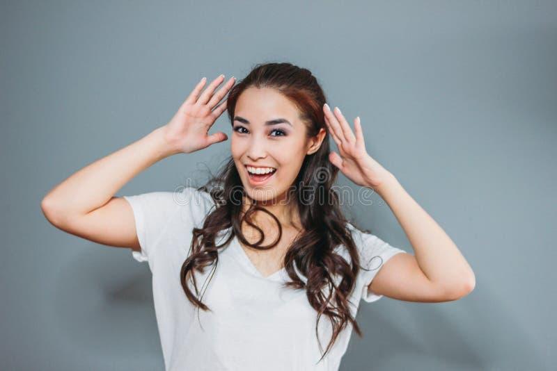 Смешной портрет счастливой азиатской молодой женщины с темными длинными волосами в белой футболке на серой предпосылке стоковое фото rf