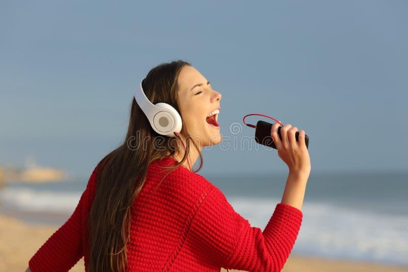 Смешной предназначенный для подростков петь и слушать к музыке на пляже стоковое фото rf