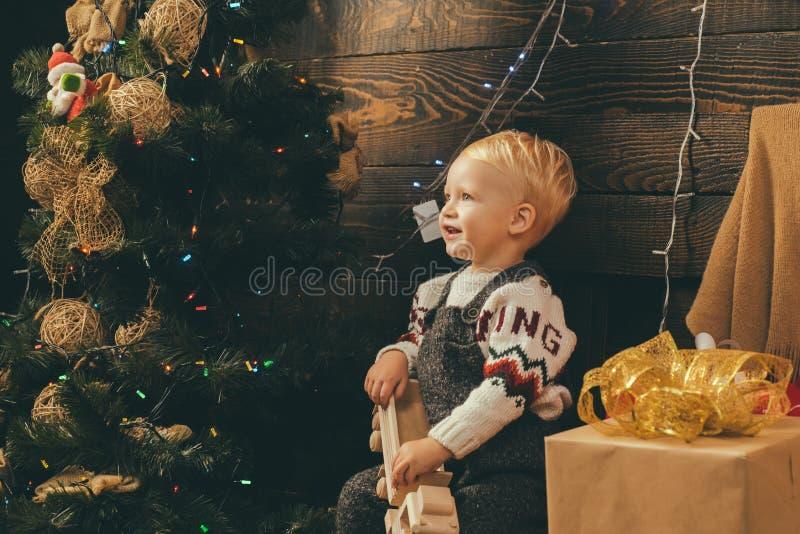 Смешной ребенк держа подарок рождества babette праздники рождества счастливые веселые Украшение рождественской елки hildren подар стоковые изображения