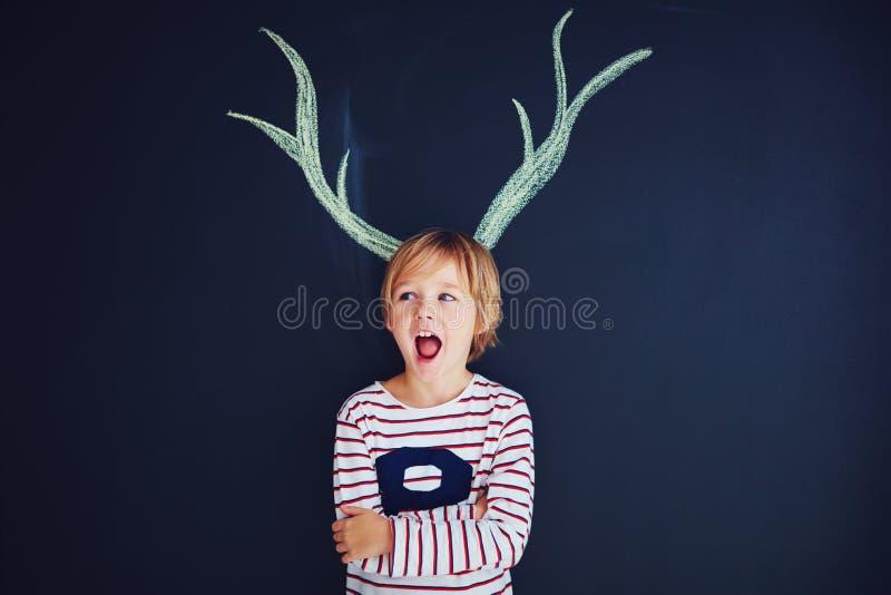 Смешной ребенк, мальчик при вычерченные antlers стоя перед стеной мела стоковая фотография