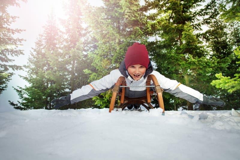 Смешной ребенк sledging на зимнем времени в лесе стоковое фото rf