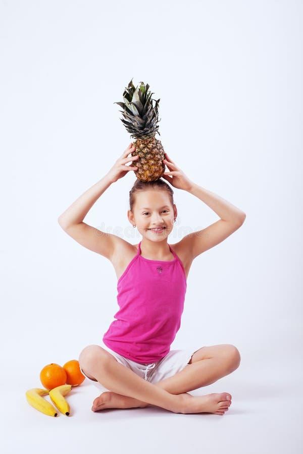 Смешной ребенок имеет апельсины, ананас и банан Концепция его стоковое изображение