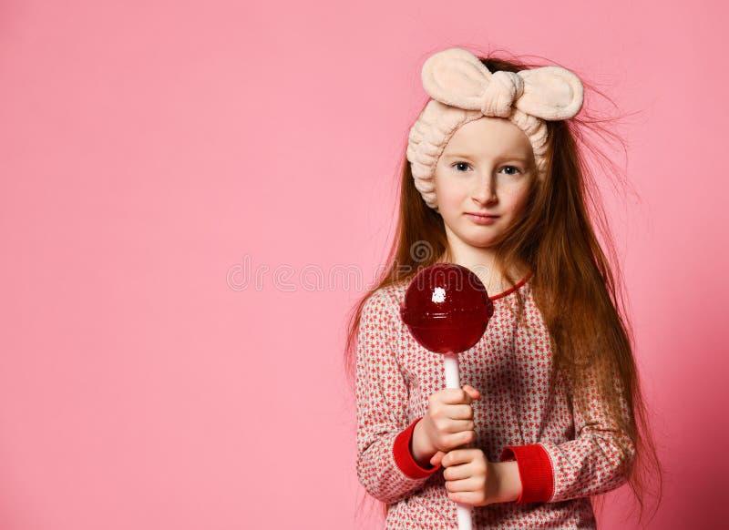 Смешной ребенок с леденцом на палочке конфеты, счастливая маленькая девочка есть большой леденец на палочке сахара стоковая фотография rf