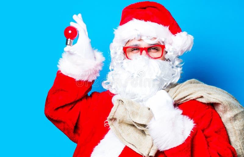 Смешной Санта Клаус имеет потеху с электрической лампочкой стоковое фото