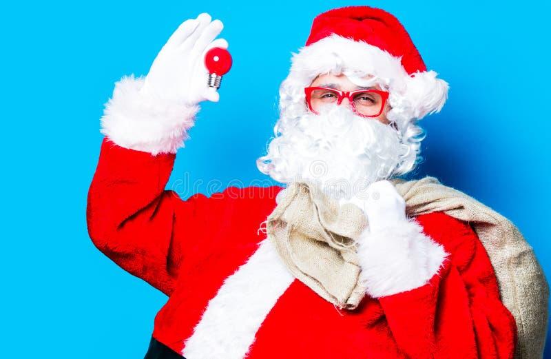 Смешной Санта Клаус имеет потеху с электрической лампочкой стоковые изображения