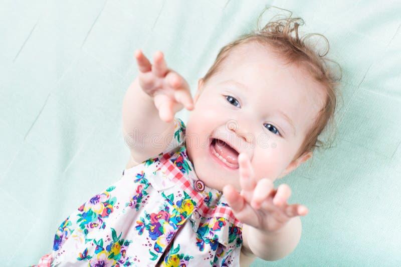 Смешной смеясь над ребёнок играя на зеленом одеяле стоковое изображение