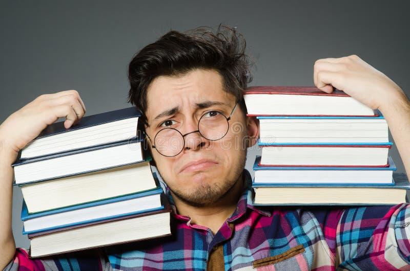 Смешной студент с много книг стоковые изображения rf