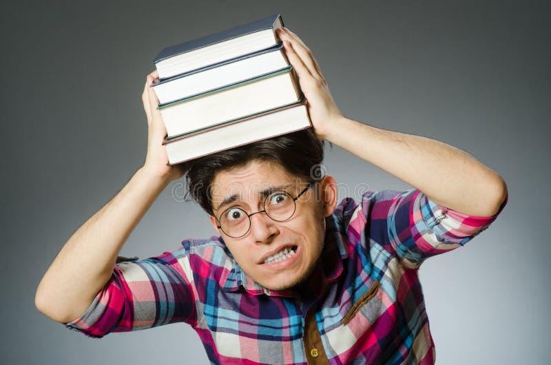 Смешной студент с много книг стоковое фото rf