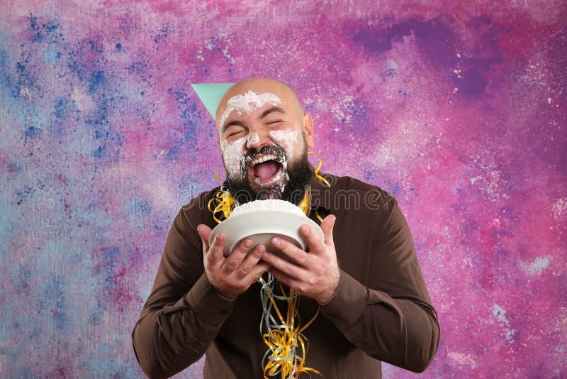 Смешной тучный человек есть именниный пирог и мажа сливк стоковое фото