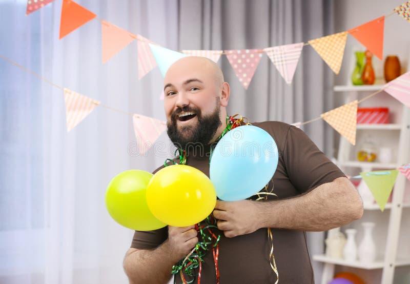 Смешной тучный человек празднуя день рождения стоковое фото