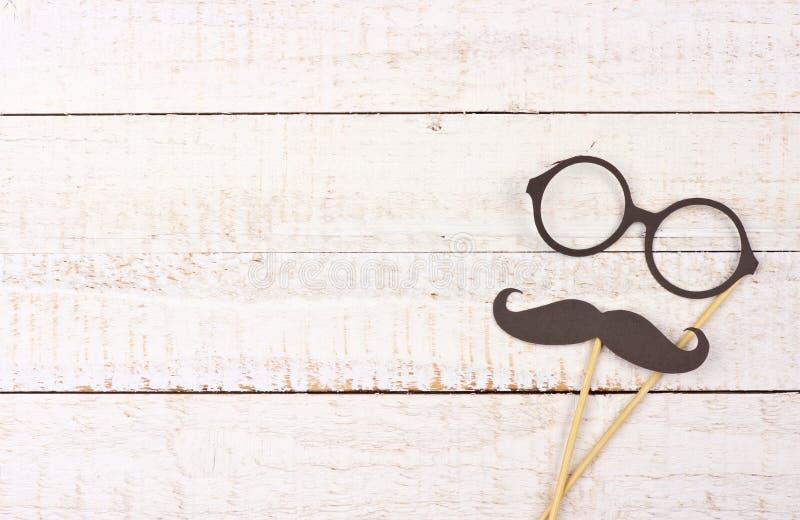 Смешной усик и стекла на ручках против белой древесины стоковое изображение
