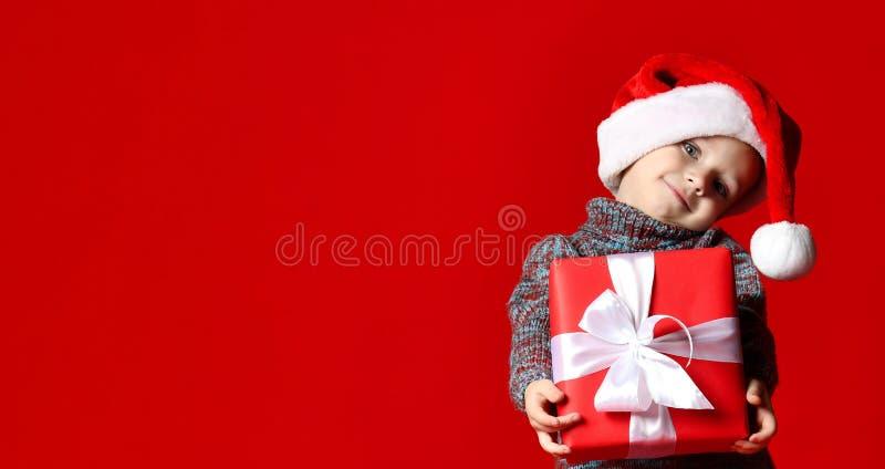 Смешной усмехаясь ребенок в шляпе Санты красной держа подарок рождества в руке стоковые фотографии rf