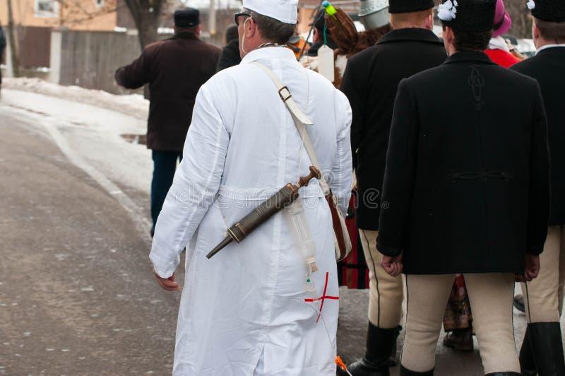 Смешной характер доктора с огромным шприцем на зиме кончая carniva Transylvanian традиционное стоковое изображение