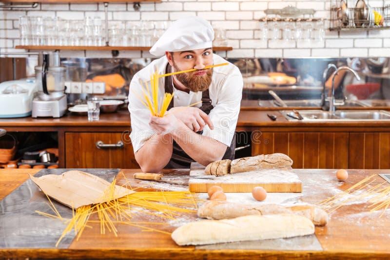 Смешной хлебопек делая усик используя macarons на кухне стоковое фото rf